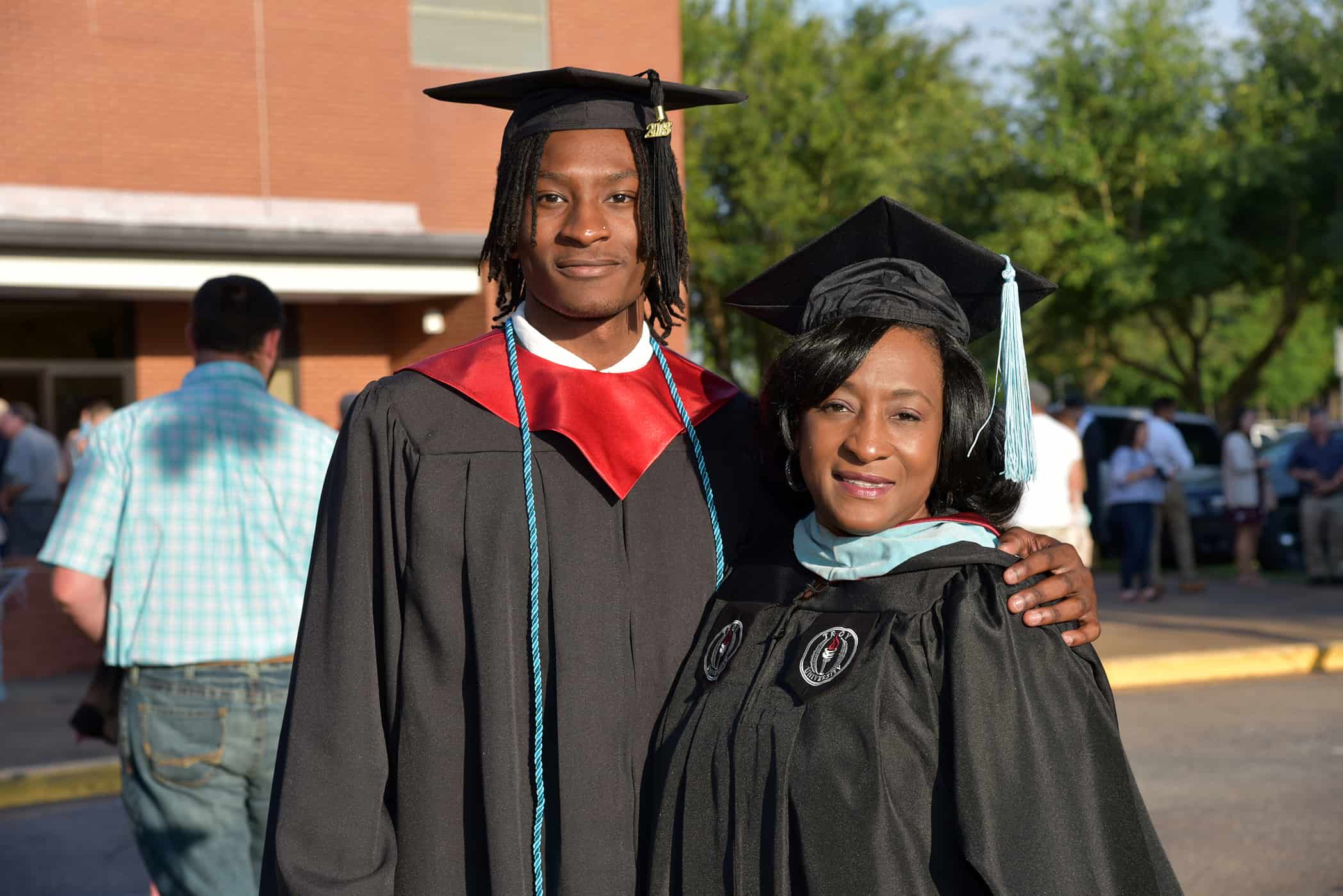 A male and female in black graduation cap and gowns stand together.