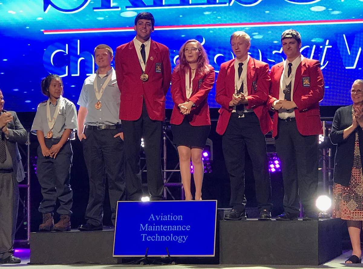 SkillsUSA gold medal recipient Bailey Mills (third from left) stands tall with the rest of the aviation maintenance technology medal winners during the award ceremony at the SkillsUSA National Leadership and Skills Conference in Louisville, Kentucky.