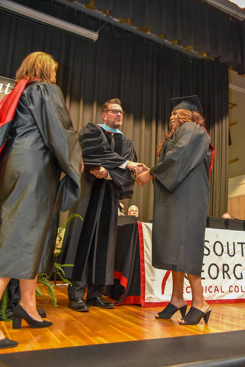 South Georgia Technical College President Dr. John Watford (center) shakes Jamera Mitchell's hand (right) as SGTC Vice President of Student Affairs Karen Werling (left) prepares to present her work study student with her associate degree diploma.