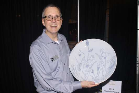 Brian Gallagher holding a platter by potter Julie Wiggins.