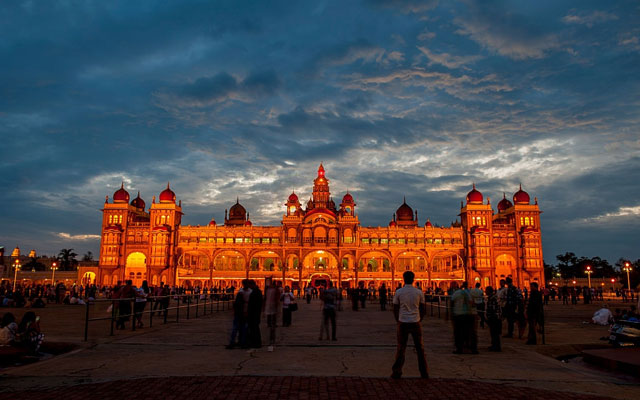 Mysore Maharaja's Palace at night with it's lights on under the dramatic sky.