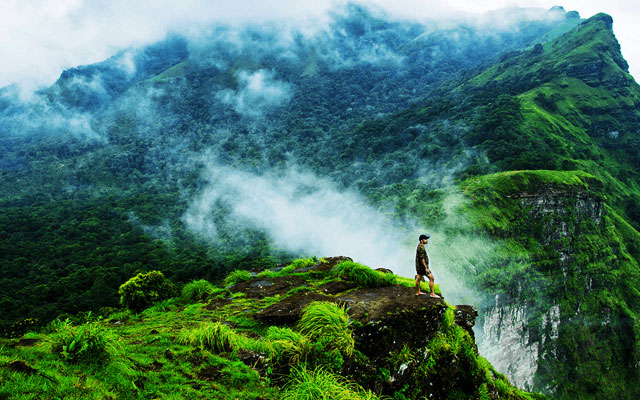 A man standing at the end point of a hill in Coorg and enjoying the scenery of Coorg hill station