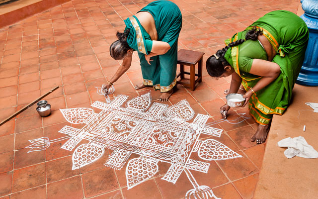 Two women paint a pattern outside her home to celebrate the Pongal festival