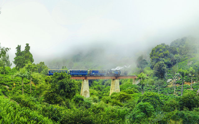Nilgiri Mountain Train in Ooty, running in the bridge between misty mountains in winter season.