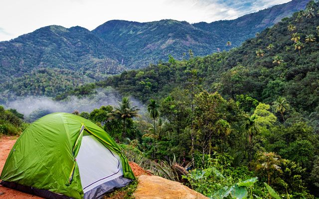 In this image solo traveller camping experience is expressed with his bike and tent. In the background hills, waterfall and green forests can be seen.