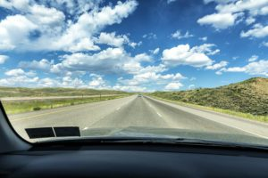 Summer travel highway road trip car point of view perspective through windshield driving on Interstate 80 expressway in the western USA state of Wyoming on a bright puffy cumulus cloud day.