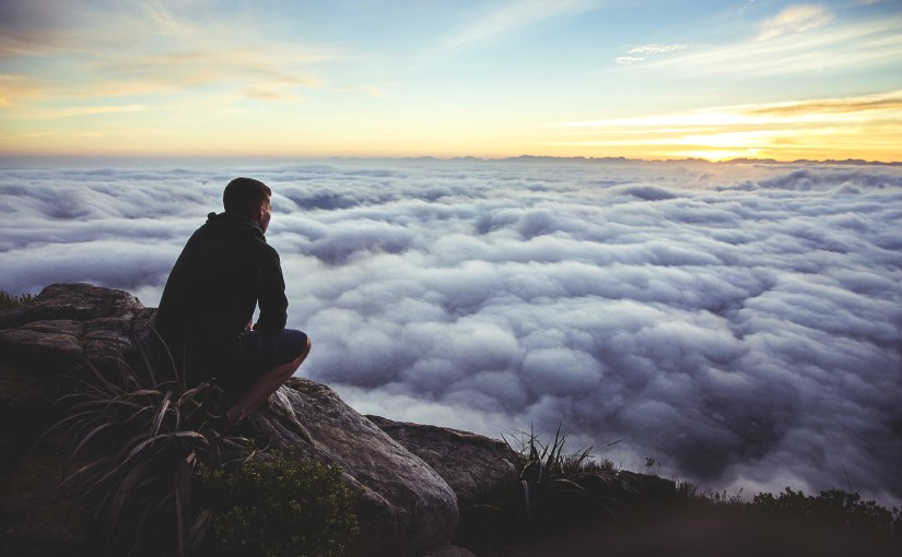 perched on rock, above the clouds at sunrise