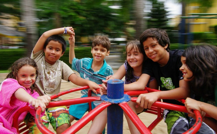 smiling kids on playground equipment