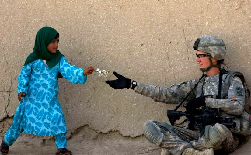 girl handing flower to soldier
