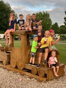 Kids posed on a wooden train in playground