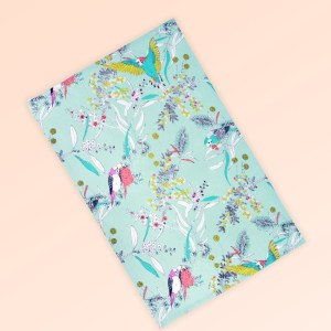 Tea towel with an aqua background and budgerigars and small native flowers in pastel colours. The fabric is a natural Australian organic cotton.