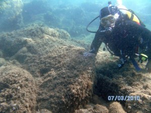 foto trasmessa per la pubblicazione da Oreste Montebello in cui si vede un sub accanto a delle macine accatastate. La foto è stata scattata nel 2010. Nel 2012 infatti l'area è stata sottoposta a vincolo e non si possono fare immersioni