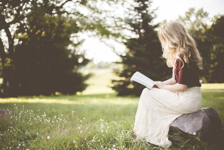 Fille qui lit un livre dans un parc. H et la plume de l'espoir