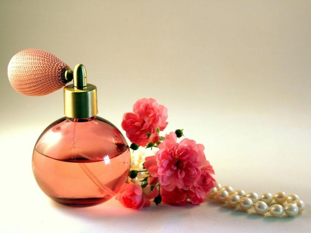 Un flacon de parfum avec des fleurs et un collier de perles