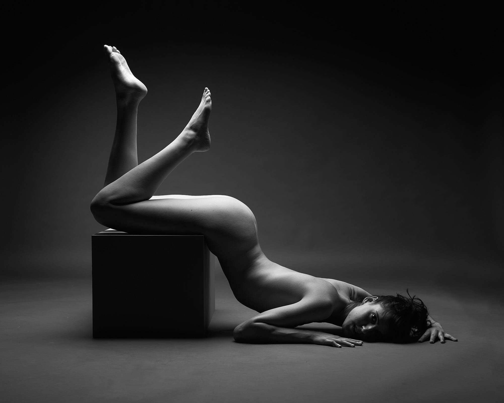 Une femme nue allongée sur un cube