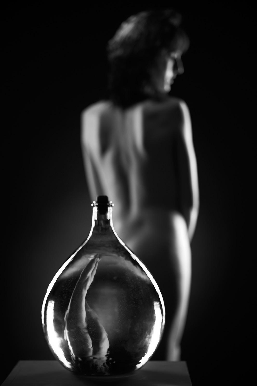 Une femme nue de dos à travers une bouteille, nu académique, artistique