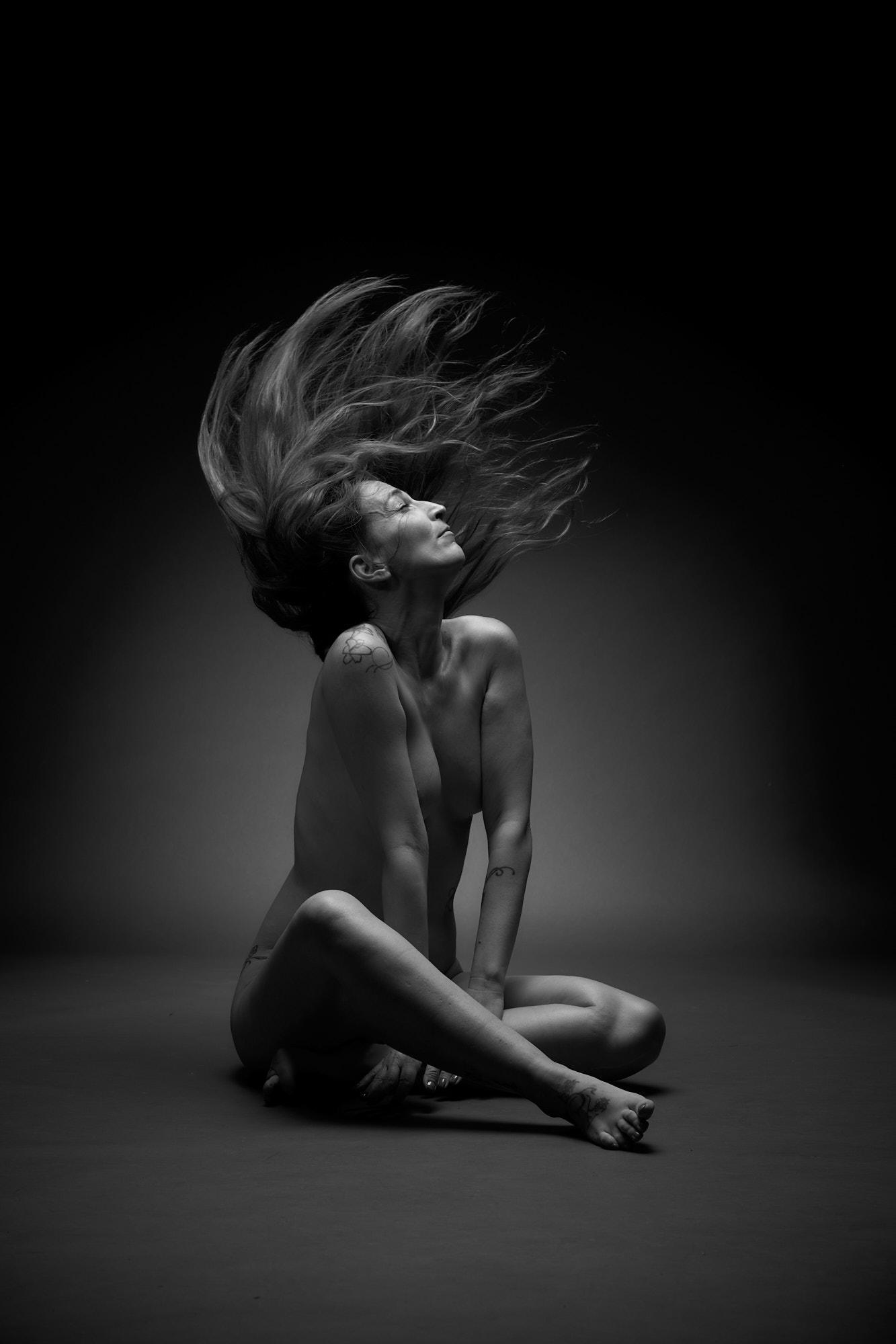Femme nue assise au sol en mouvement