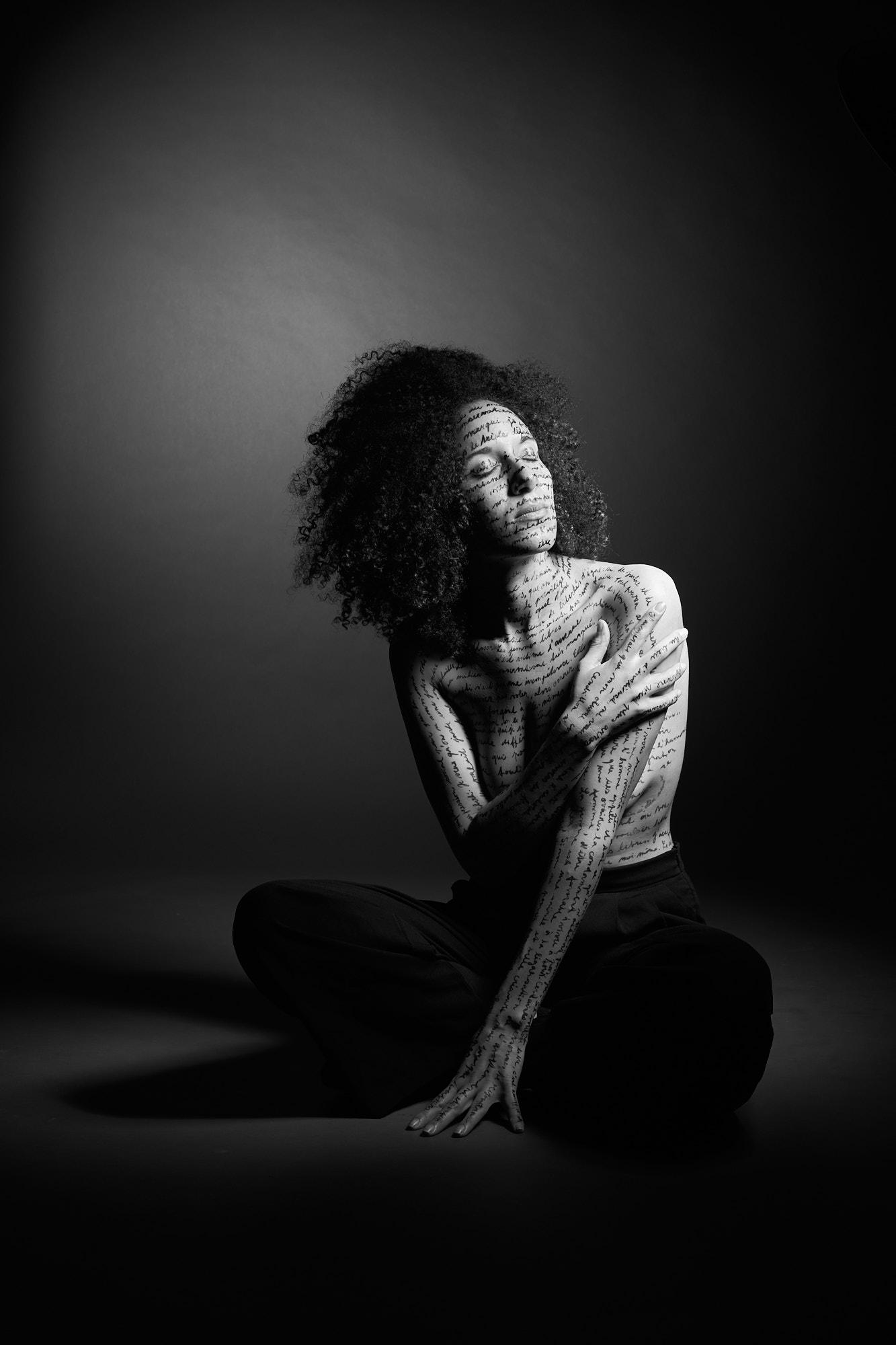 Une femme assise, écriture sur le corps