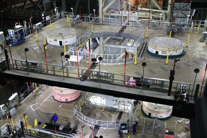 NASA's twin five-segment solid rocket boosters for the agency's first Space Launch System are being stacked at Kennedy Space Center. Only two more segments remain before booster stacking is complete. Credit: NASA