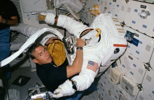 As 51I's ambitious space salvage operation took shape, one thing was certain: the mission would be EVA-intensive and RMS-intensive. Pictured on Discovery's middeck with one of the space suits, astronaut Bill Fisher would perform delicate electrical work on the crippled Leasat-3 (Credits: NASA).