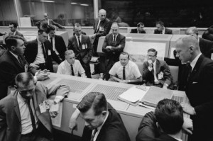 Flight controllers—with Flight Director Chris Kraft seated at center—watch their monitors in dismay after the loss of the Agena on 25 October 1965. The incident led to the development of a new plan to fly a rendezvous mission between two manned craft, Gemini VI-A and Gemini VII (Credits: NASA).