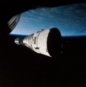 Backdropped by the grandeur of Earth, Gemini VII drifts serenely in the inky darkness (Credits: NASA).