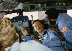 "61C crewmen Steve Hawley, Robert ""Hoot"" Gibson (facing camera), and Charlie Bolden demonstrate the cramped nature of Columbia's flight deck during the mission (Credits: NASA)."