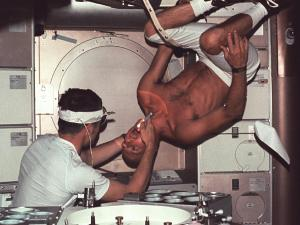 Skylab 2 commander Pete Conrad undergoes a dental examination by medical officer Joseph Kerwin in the Skylab Medical Facility. In the absence of an examination chair, Conrad simply rotated his body to an upside down position to facilitate the procedure. (Credits: NASA).