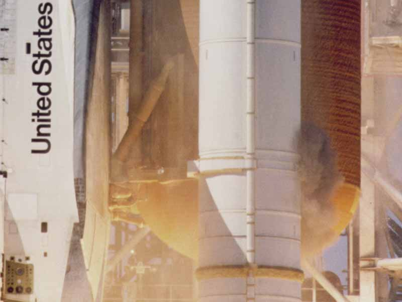 A plume of grey smoke near the aft attach strut on the right Solid Rocket Booster. - Credits: NASA.