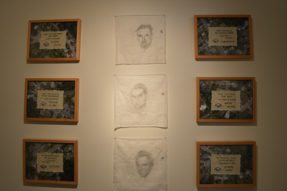 """Works by Tatiana Garmendia: Middle Row: Dr. Jose Manuel Garmendia Sr., Abuelo, Dr. Jose Manuel Garmendia Jr., Papi & Dr. Jose Manuel Garmendia Sr., Hermano, 16"""" x 16"""", graphite on distressed cotton handkerchief, 2017. Outer Rows: In A Green and Peaceful Neighborhood (six panels), 2017, 13"""" x 17"""" each, embroidered doilies on aerial photographs. Serving as surrogates for the domestic domain, each of the embroidered doilies testifies to the brutal disruption the artist's family suffered when the father was forcibly removed by authorities. Mounted on aerial drone photographs of local suburban neighborhoods, they signal it can happen anywhere, anytime. Geographical differences and generational distance between persecuted groups vanish in light of human suffering."""