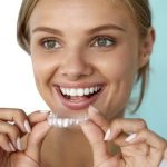 fees at Whitchurch shows Young woman holding Invisalign braces