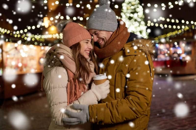 If breath smells bad, then it's hard to get close like the couple in this winter scene of a man and a woman cuddling in a scene with winter lights and warm clothes.