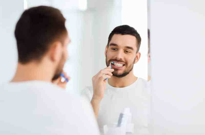 Man with tidy tooth brushing kit in a white bathroom