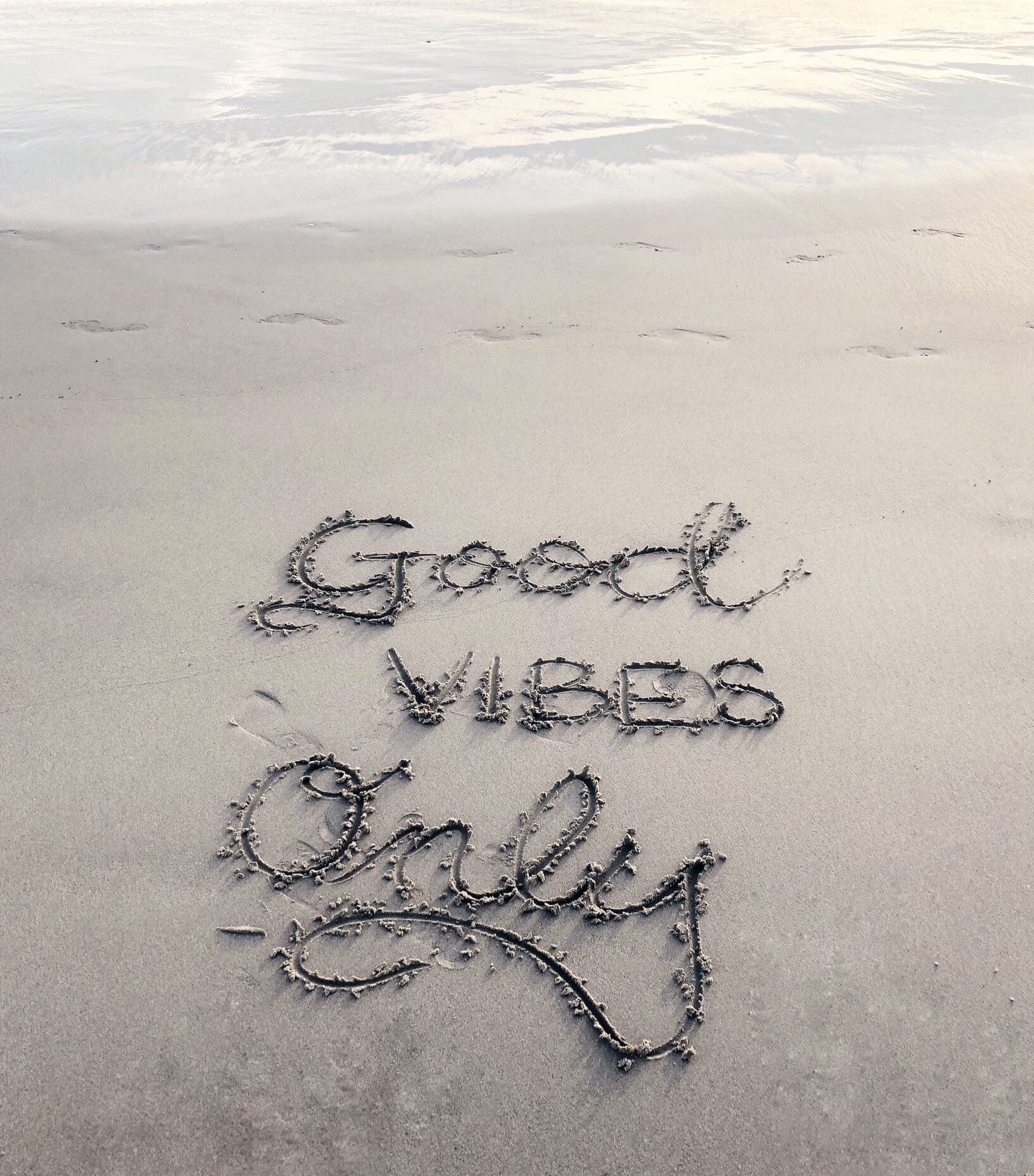 Good Vibes only written in beach sand