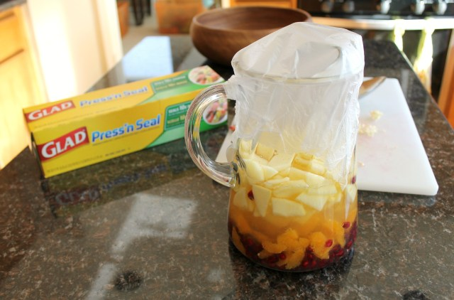 A large glass pitcher with wine and fruit covered with press'n seal plastic wrap.