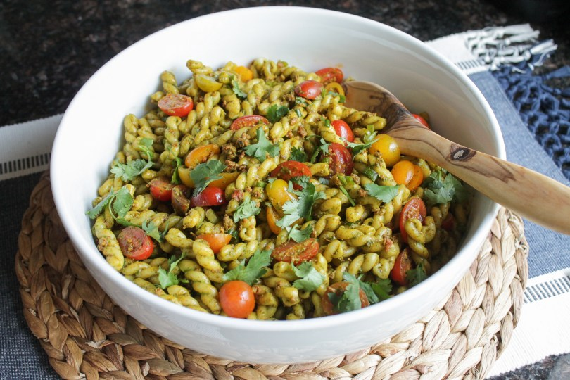 Pasta salad in a white bowl with wooden serving spoon.
