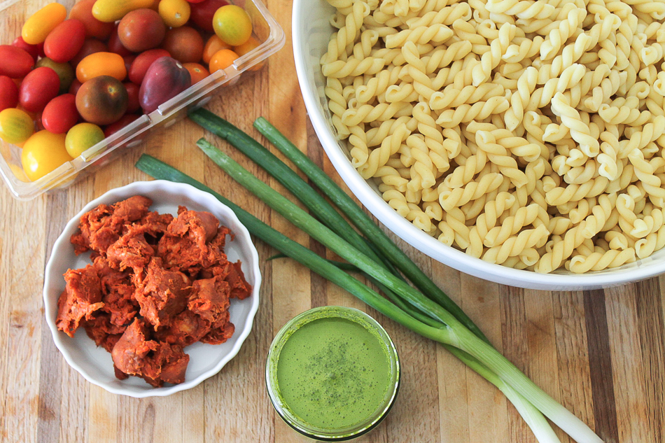 Cooked pasta in a bowl, green onion stalks, cilantro dressing in a glass jar, crumbled raw longaniza, sweet cherry tomatoes.