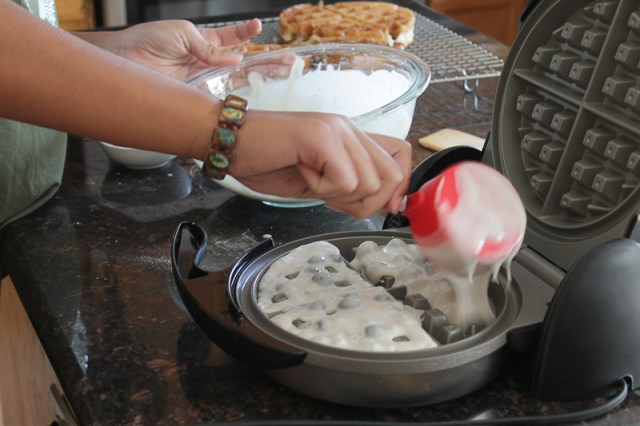 A hand pouring blueberry waffle batter into a hot waffle maker with cooked waffles in the background.