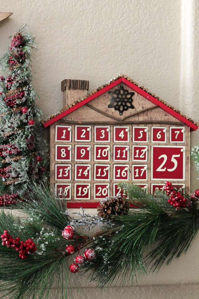 Advent calendar house with 25 doors placed on a mantel with Chrismas decor.