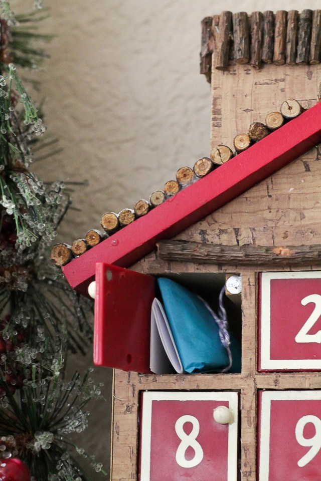 Advent calendar miniature house with one door open showing a wrapped toy and folded note.