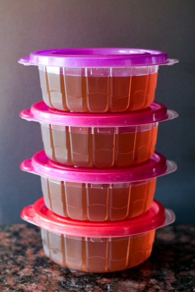Four plastic containers filled with vegetable broth, stacked on top of each other.