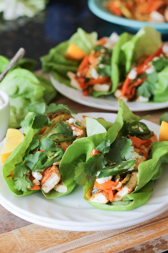 Sautéed tofu and vegetables wrapped in butter lettuce leaves, topped with sliced serrano chiles and cilantro sprigs.