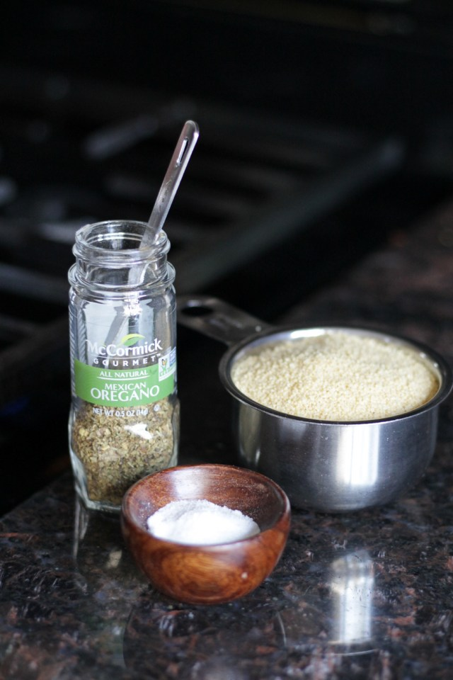 McCormick bottle of Mexican oregano, couscous in a measuring cup, small wooden bowl with salt.