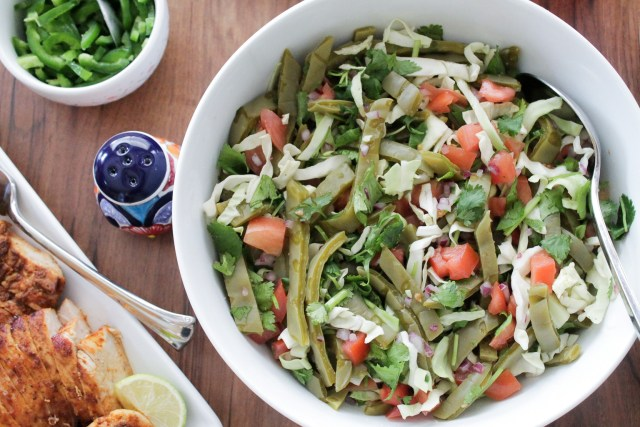 Cooked cactus salad with cabbage and tomatoes in a white serving bowl on a dinner table with other sides.