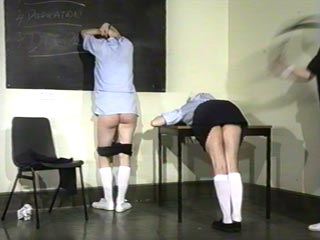 The gym mistress begins by spanking both girls over her knee, then straps their naughty bottoms