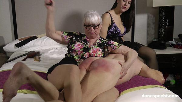 Dana Specht holds husband, Lee, in a leg lock while she gives him a severe paddling