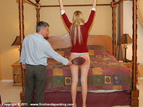 Very tall Adrienne Black wears heels and reaches above her head as her bare bottom feels the leather paddle
