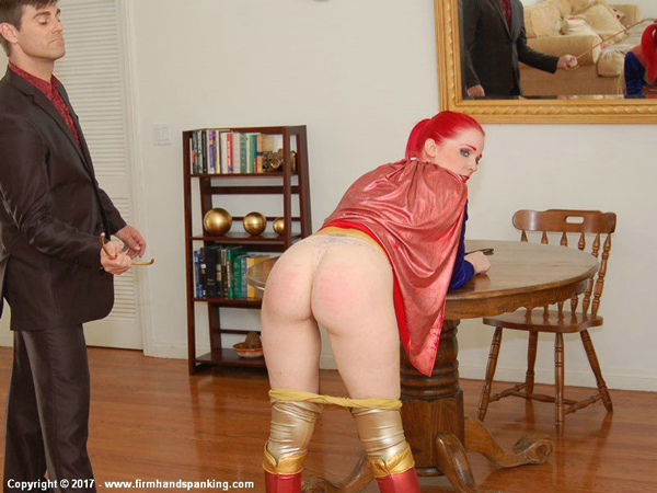 Alison Miller dresses up as Supergirl and bends over the table for a cosplay caning