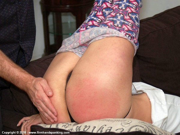 Closeup of Delta Hauser's bottom getting spanked in the diaper position