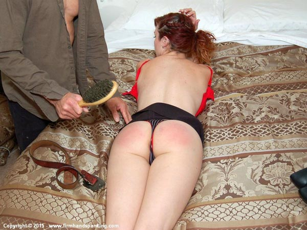 Stacy Stockton laying face down on the bed for her hairbrush punishment
